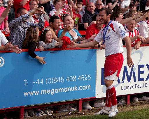 Stevenage Borough's Lawrie Wilson gives his promotional T-shirt to a young fan